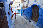 Young muslim boy in the old medina of Chefchaouen, Morocco.