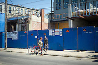 Two pedestrians pass new construction   in the Bushwick neighborhood of Brooklyn in New York on Saturday, April 27, 2013. The neighborhood is undergoing gentrification changing from a rough and tumble mix of Hispanic and industrial to a haven for hipsters, forcing many of the long-time residents out because of rising rents.  (©Frances M. Roberts)