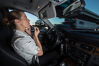 A businesswoman applies makeup and talks on her mobile smart phone as oncoming traffic speeds by while navigating IH-35 clogged highway in Austin.