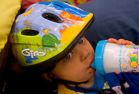 A toddler sips from a cup while riding along on a mountain biking trip around Grand Island National Recreation Area in Munising Michigan.