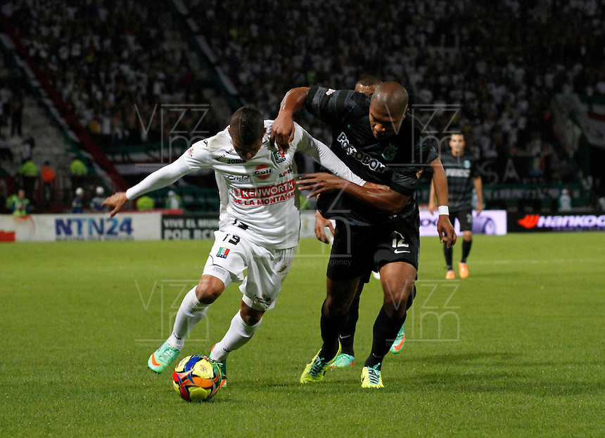 MANIZALES -COLOMBIA-22-03-2014. Cesar Arias (Izq) de Once Caldas disputa el balón con Alexis Henriquez (Der) del Atletico Nacional en partido por la fecha 12 de la Liga Postobón I 2014 jugado en el estadio Palogrande de la ciudad de Manizales./ Once Caldas player Cesar Arias (L) fights for the ball with Atletico Nacional player Alexis Henriquez (R) during match valid for the 12th date of the Postobon League I 2014 played at Palogrande stadium in Manizales city.  Photo: VizzorImage/Santiago Osorio/STR