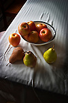 Apple and pears on white table cloth in bowl.