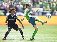 Seattle Sounders FC forward Alvaro Fernandez kicks the ball away from New England Revolution defender Kevin Alston during play at .CenturyLink Field in Seattle Sunday June 26, 2011. The Sounders won the game 2-1.   during play between the Seattle Sounders FC and the New England Revolution at .CenturyLink Field in Seattle Sunday June 26, 2011. The Sounders won the game 2-1.