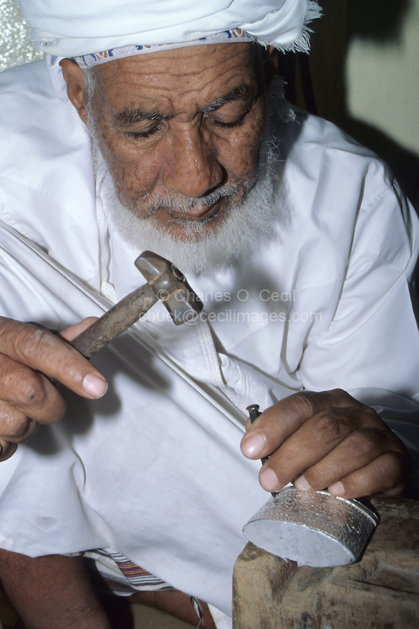 Rustaq, Oman, Arabian Peninsula, Middle East - One of Oman's foremost silversmiths, Rashid Obeidani, hammers a design into the casing of a silver khanjar, Oman's traditional curved dagger.