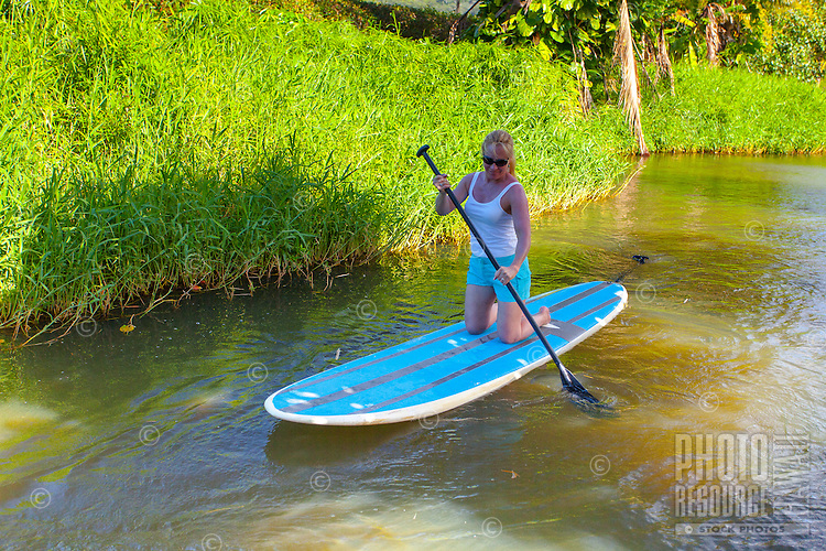 Blond woman with sunglasses kneels while standup paddleboarding on the Hanalei River, Kaua'i