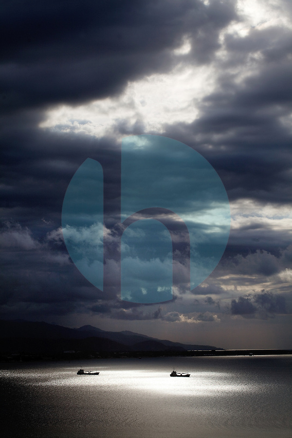 October 25th, 2012_Dili, TIMOR-LESTE_ The sun Illuminates container ships anchored off the coast of the Timorese capital of Dili, as it finds its way through afternoon storm-clouds.  Photographer: Daniel J. Groshong/Tayo Photo Group