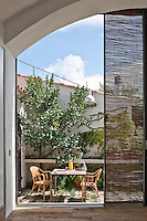 A sliding glass door opens onto a small patio furnished with an outdoor table and garden chairs