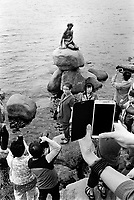 Denmark. Capital Region. Copenhagen. Asian tourists and the Little Mermaid, which is a bronze statue by Edvard Eriksen, depicting a mermaid. The sculpture is displayed on a rock by the waterside at the Langelinie promenade. It is 1.25 meters tall and weighs 175 kilograms. Based on the fairy tale of the same name by Danish author Hans Christian Andersen, the small and unimposing statue is a Copenhagen icon and has been a major tourist attraction since 1913. 3.08.2016  © 2016 Didier Ruef