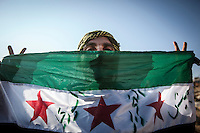 An opossition fighter of the Free Army holds a flag of the FSA as he makes the signal of victory at one of the a new training camps established at the top of the mountains in northern Idlib.