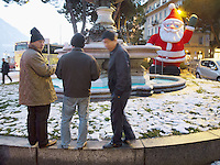 Switzerland. Canton Ticino. Lugano. Three chinese tourists stand near an inflatable Santa Claus and a water fountain. Snow on the grass. 16.12.12 © 2012 Didier Ruef