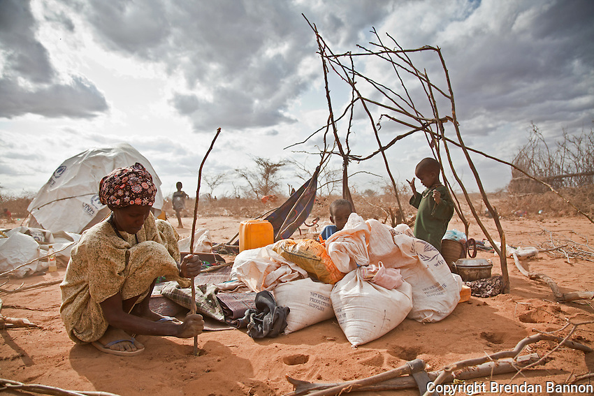 A refugee uses twigs and craps of material to build a shelter for her family. There is no room for most new arrivals in the Dadaab camps, so the thousands of people who arrive every week must carve out a place for themselves in the surrounding desert. Doctors Without Borders estimates that by the end of 2011 there will be 500,000 people living in and around the camps, which were originally built to accommodate 90,000.