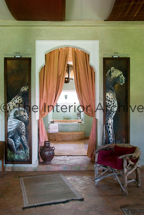 Two large animal paintings frame the view through abundant curtains of an alcoved bath lit by a skylight at Le Palais Rhoul