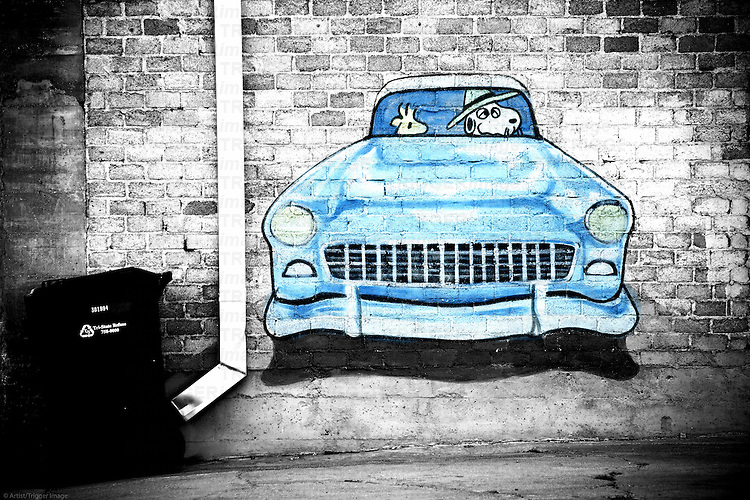 Graffiti of the cartoon character Snoopy in a car in a prominent wall.
