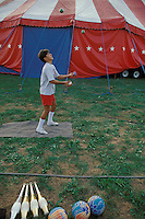 "Young boy practices juggling in circus ""back yard"" Bentley Bros. circus, one of the few remaining ""mud show"" circus performing under a canvas big top."