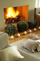 A row of candles are lined up in front of three box-hedge like arrangements of pine and olive branches before a roaring fire in the living room