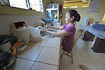 In Abucay, a seaside town in the Philippines province of Bataan, Ellen Bundang washes dishes in her home. Born with abnormal legs, she is a member of the local Persons with Disabilities (PWD) organization.
