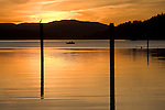 Sunset over Lake coeur D Alene, Idaho, from Wolf Lodge Bay with old pilings, a fishing boat and a perched bird.