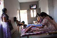 A surrogate looks under her pillow at her mobile phone and other belongings while other surrogates laze around and chat with each other, as they spend the entire pregnancy, in the surrogate's house in Anand, Gujarat, India on 11th December 2012. Photo by Suzanne Lee / Marie-Claire France