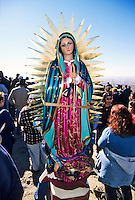 A large, colorful statue, or bulto, of the Virgin of Guadalupe ascends a mountain strapped to the back of a pilgrim during the annual Virgin of Guadalupe Feast Day celebration at the village of Tortugas, near Las Cruces, New Mexico