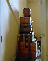 An attic corridor is piled high with vintage trunks, suitcases and hat boxes