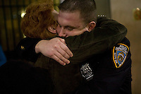Newly sworn in Police Officer Kyle Smith (R) hugs his aunt retired OCCB detective Stefanie Rich after graduating with the NYPD Class of 2005, December 29, 2005, in New York City. 1,735 new police officers were sworn in during the ceremony.