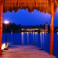 The restaurant and bar, El Cantarito, seen from the seaward side of the lagoon and illuminated by candlelight at dusk