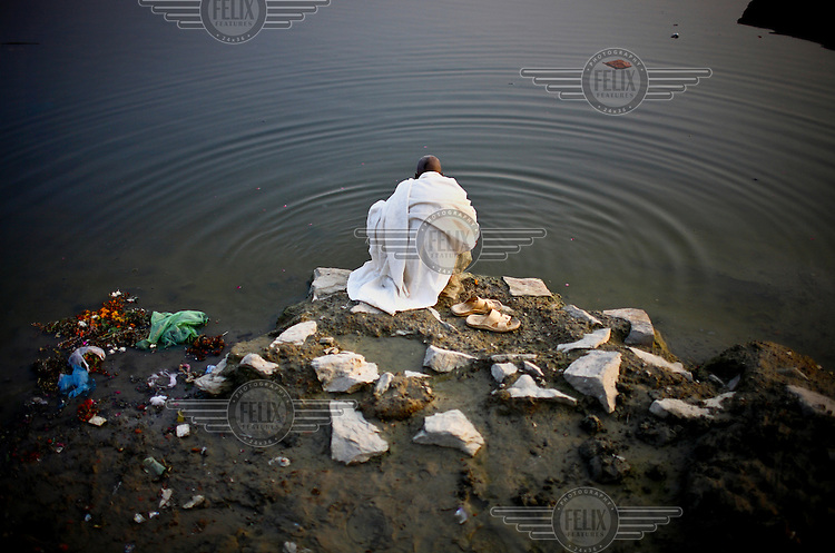 A man leans over the Ganges River in Varanasi.