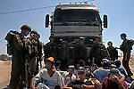 Protesting Israeli settlers block a truck carrying an army bulldozer from leaving the scene where houses are being demolished, at the Israeli settlement bloc of Gush Katif, Gaza Strip.<br /> Israeli army demolished a row of old Egyptian houses, to prevent their renovation by hardline Israeli settlers who recently moved-in to Gush Katif in order to resist Israel's upcoming pullout from Gaza.