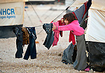 Early in the morning, a girl reaches out of her tent for clothing hung out to dry in the Zaatari Refugee Camp, located near Mafraq, Jordan. Opened in July, 2012, the camp holds upwards of 50,000 refugees from the civil war inside Syria, but its numbers are growing. International Orthodox Christian Charities and other members of the ACT Alliance are active in the camp providing essential items and services.