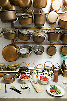 Numerous copper pots hanging from the wall in the kitchen of the restaurant E Curti in Santa Anastasia, Italy