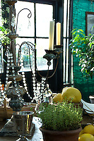 View inside one of the greenhouses with antique crystal candelabra, lemons and herbs