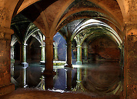 """General view of Manueline Cistern of the El Jadida (Mazagan) fortress, built by Francisco and Diogo de Arruda, 16th century, El Jadida, Morocco. El Jadida, previously known as Mazagan (Portuguese: Mazag""""o), was seized in 1502 by the Portuguese, and they controlled this city until 1769. The underground Cistern was originally designed to store munitions. It served as a fencing school before being used after completion of the town walls in 1541 as a tank to store water. The symmetrical construction has a vaulted roof supported by 25 circular and rectangular pillars, with just one central window in the ceiling, 3.5 m in diameter, producing a single shaft of light. The shallow sheet of water produces a shimmering reflection of the vaulted ceiling in the light. Picture by Manuel Cohen"""