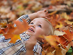Two year old girl lying on fallen tree leaves in autumn nature