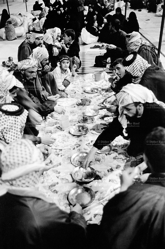 "Iraq. Najaf. A group of Iraqi pilgrims (men, women and children) pray near the entrance to the mosque, Holy Shrine of Imam Ali. They celebrate the religious commemoration of Muharram which is a month of remembrance that is often considered synonymous with the event of Ashura. Ashura, which literally means the ""Tenth"" in Arabic, refers to the tenth day of Muharram. It is well-known because of historical significance and mourning for the martyrdom of Hussein ibn Ali, the grandson of Muhammad. Shi'a Muslims start the mourning from the 1st night of Muharram and continue for two months and eight days. However the last days are the most important since these were the days where Hussein and his family and followers were killed in the Battle of Karbala which took place on Muharram 10, in the year 61 of the Islamic calendar (October 10, 680). Muharam's month is considerated as one of the most important feast for the Shiism branch of Islam. Shia Islam is the second largest denomination of Islam.The followers of Shia Islam are called Shi'ites or Shias. 26.02.04 © 2004 Didier Ruef"