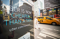 An advertisement on a telephone kiosk for Uber in Midtown in New York on Wednesday, July 30, 2014.  The livery service Uber has announced that it has temporarily reduced its prices for its UberX service in New York making a ride cheaper than a yellow, metered New York taxicab. The promotion is an attempt to garner a larger share of the livery market. (© Richard B. Levine)