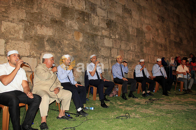 Palestinians attend a ceremony in front of Damascus gate in Jerusalem's old city during the holy fasting month of Ramadan on June 25, 2016. Ramadan is sacred to Muslims because it is during that month that tradition says the Koran was revealed to the Prophet Mohammed. The fast is one of the five main religious obligations under Islam. More than 1.5 billion Muslims around the world will mark the month, during which believers abstain from eating, drinking, smoking and having sex from dawn until sunset. Photo by Mahfouz Abu Turk