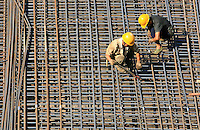Workers attaching steel rods to build a foundation, Beijing, China