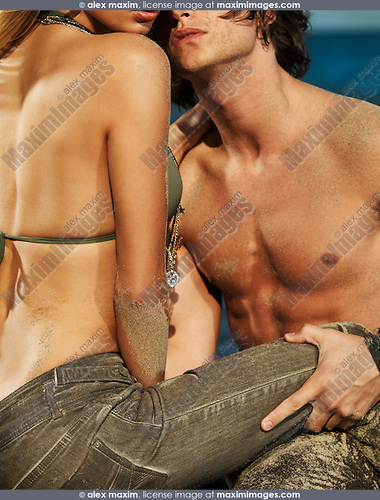 Romantic young couple with sand on their bodies kissing at the beach