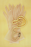 Pair of white nylon ladies see-through gloves lying on antique paper with pearl necklace