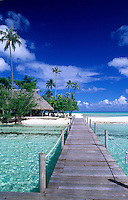 Wooden dock walkway over tropical water thatched hut cottagein beautiful Tahiti, Bora Bora, French Polynesia, South Pacific holiday