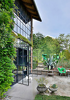 The exterior of a modern house with a full height glass window with double doors leading to a terrace area outside.