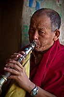 A Buddhist monk plays a traditional wind instrument.