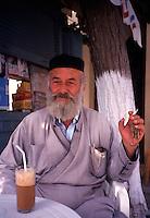 Greece. Crete. Episkopi Village Priest, sat with his Frappe
