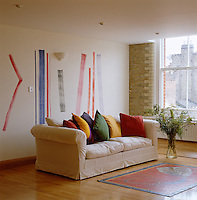 The colours of the cushions on the sofa echo the coloured lines painted on the rear wall of this otherwise white living space