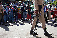 A police officer keeps a crowd at a distance from a polling station during presidential and legislative elections in Port-au-Prince, Haiti.