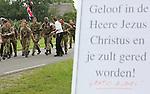 Foto: VidiPhoto<br /> <br /> VALBURG - Met onder meer tekst als &quot;Jezus redt! Gelooft in Hem!&quot;, werden de wandelaars van de Vierdaagse van Nijmegen dinsdag begroet in Valburg. Het kerkdorp ligt halverwege de Vierdaagseroute in de Betuwe. Enkele predikanten, onder leiding van de  plaatselijke hervormde predikant ds. B. van Leeuwen, grepen de doorkomst van 40.000 wandelaars aan om ze met het evangelie van Jezus Christus in aanraking te brengen. De Vierdaagsedeelnemers konden een gratis Lukas-evangelie krijgen of -na later contact- een complete Bijbel. Opmerkelijk waren de vele positieve reacties, ook van de buitenlandse wandelaars, ondanks de onverwachte confrontatie met het geloof. Dinsdag was de eerste dag van de 98e editie van de Nijmeegse Vierdaagse -het grootste wandelevenement ter wereld- die traditiegetrouw door de Betuwe gaat.
