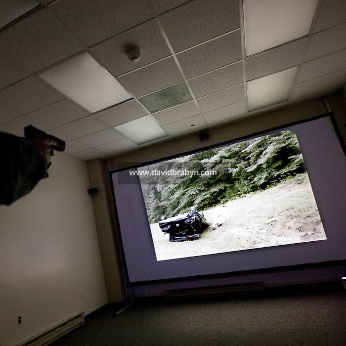 A person aims a gun at a screen during a session on the Fire Arms Training Simulator (or FATS) at the FBI National Academy in Quantico, VA, USA, 12 May 2009.