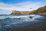 Ocean watcher.  Yaquina head lighthouse with rocky beach in foreground. Located near the town of Newport on the state of Oregon's Coast. This lighthouse is the tallest in the state of Oregon, and also one of the most popular in the United States. It is 93 feet tall and is 162 feet above sea level, and was built in 1873