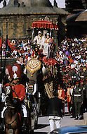 February 24th, 1975. Kathmandu. Nepal. The Coronation of King Birendra and Queen Aishwarya of Nepal, on the chosen day. At 8:37 a.m., the precise moment selected by court astrologers more than a year before, the royal priest placed the huge jewel-encrusted crown on the King's head and a diamond tiara atop Queen Aishwarya's. They were both massacred by their son Dipendra  on 1 June 2001. The King and the Queen are taking place on the Royal elephant for the coronation parade.