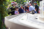 Guests watch as a live steamer model train is demonstrated by members of the Bay Area Garden Railway Society.